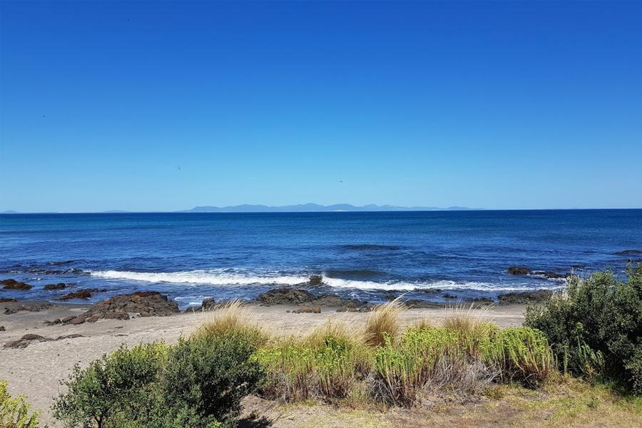 szenisches Foto des Ozeans und des Strandes mit blauem Himmel