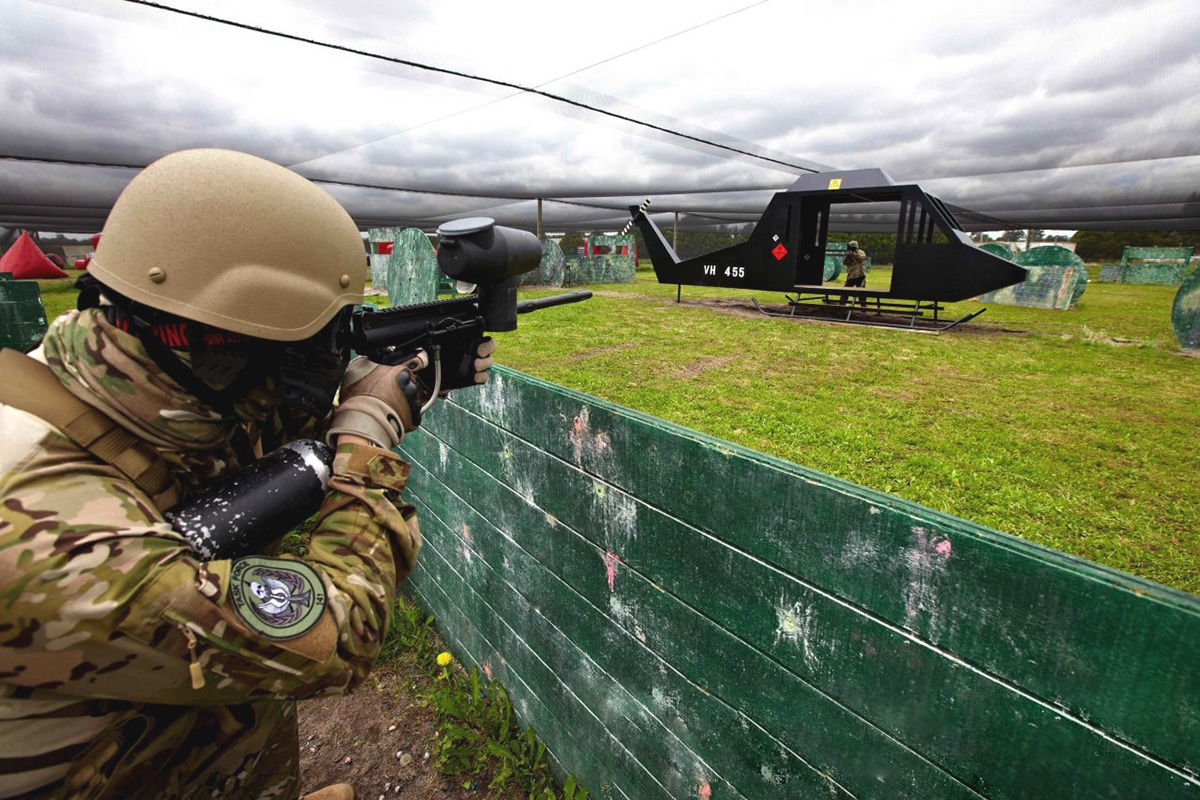 Scharfschützen den Paintballspieler aimes am Hubschraubermodell